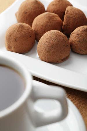 trufas de chocolate: Trufas de chocolate en el plato cuadrado blanco y una taza de caf� Foto de archivo
