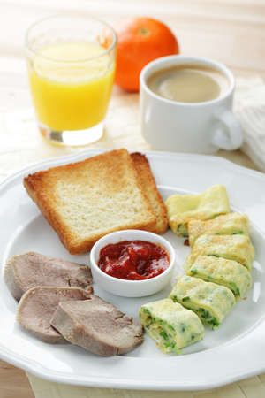 Breakfast with omelet, veal tongue, toasts, tomato sauce, coffee, and orange juice photo