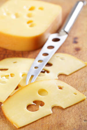 cheese knife: Sliced cheese and cheese knife on the wooden cutting board Stock Photo