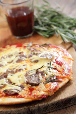 Pizza with lamb meat, cheese, and rosemary photo