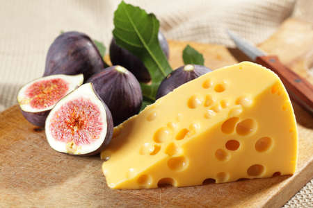 purple fig: Yellow cheese and fresh figs on the wooden cutting board Stock Photo