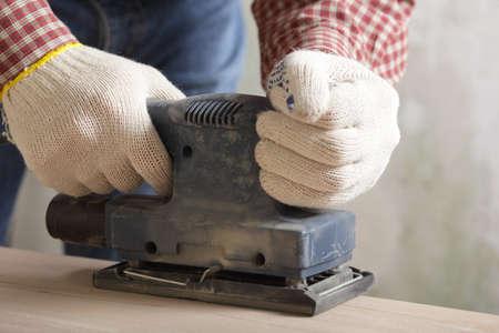 Carpenter sanding the wooden plank using power tool photo
