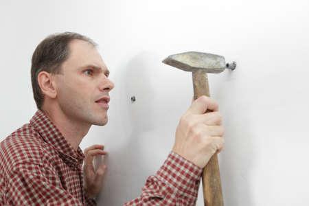 plumb: Worker hammering the wall plumb