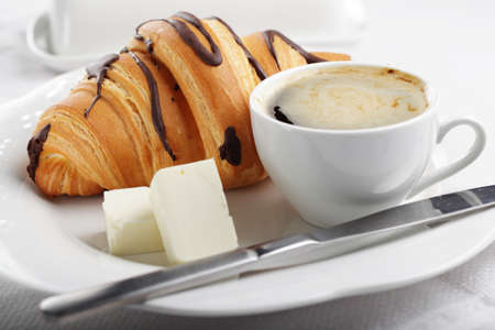 Breakfast with croissant, butter, and coffee