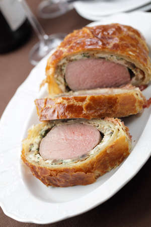 Slices of rare Beef Wellington on the serving dish photo