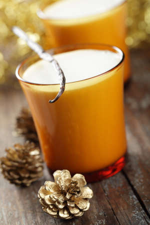 Eggnog in the yellow glass with vanilla stick and Christmas decorations