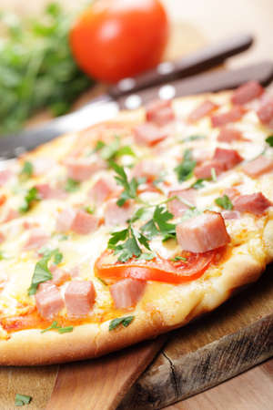 cheese pizza: Pizza with diced ham and vegetables on the cutting board