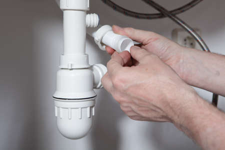 water pipes: Plumber installing the drain for the kitchen sink