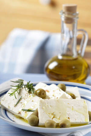 Slices of feta cheese with green olives and olive oil photo