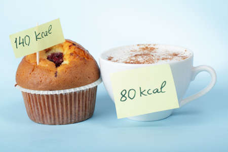 comida chatarra: Taza de caf� y el bollo de ar�ndanos con etiquetas de conteo de calor�as