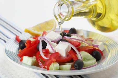 plato de ensalada: Ensalada griega y verter aceite de oliva closeup