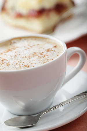 Cup of cappuccino with cinnamon against the cake