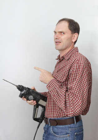 power drill: Construction worker with power drill in doubt