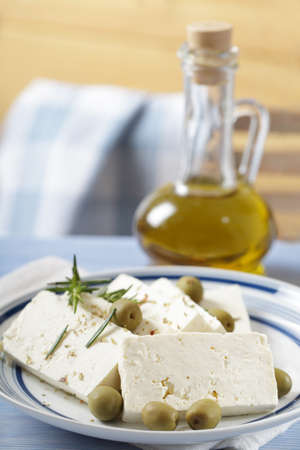 feta: Slices of feta cheese with green olives and olive oil