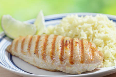 Grilled chicken breast with rice and lime photo