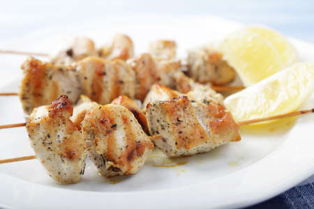Chicken souvlaki on wooden skewers with lemon. Shallow DOF