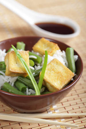 Fried tofu with rice, string bean, and soy sauce photo
