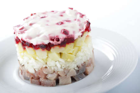 Russian herring salad with potatoes and beetroot on the white plate closeup Stock Photo - 9727286