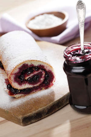 swiss roll: Swiss roll with black currant jam under powdered sugar Stock Photo