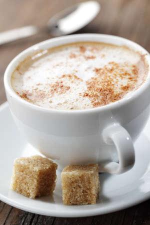 sugar powder: Cup of cappuccino with cinnamon and brown sugar closeup Stock Photo