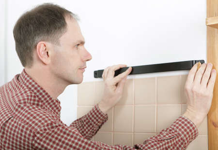 Man installing the magnetic knife rack on a kitchen wall Stock Photo - 9820281
