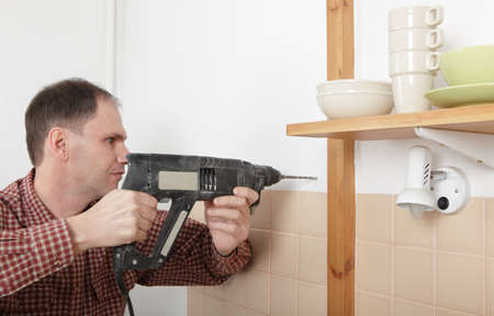 a drill: Man with power drill drilling the hole in a kitchen wall