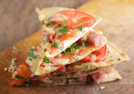 tortilla: Stack of tortilla pizza slices on the wooden cutting board