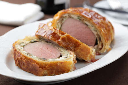 Slices of rare Beef Wellington on the serving dish