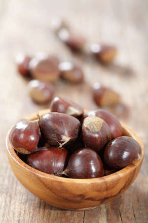 Sweet chestnuts in the wooden bowl on the rustic table photo