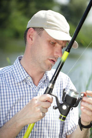 Fisher with rod on a river in sunny summer day photo