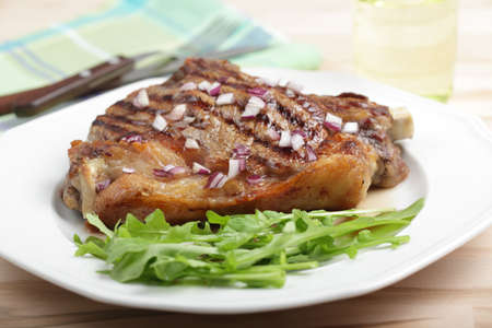 red onion: Grilled rib steak with red onion and rocket salad Stock Photo