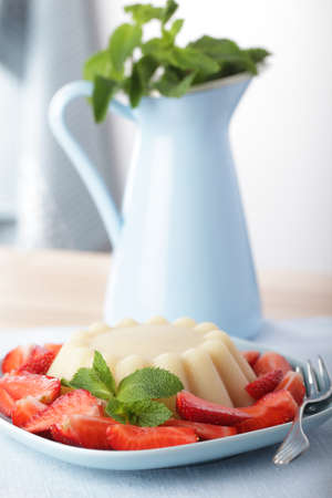 Semolina pudding with sliced strawberry and peppermint photo