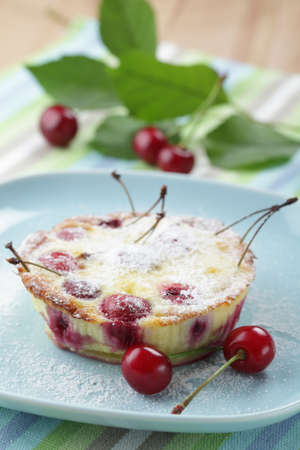 Clafoutis with sour cherry on the plate closeup photo