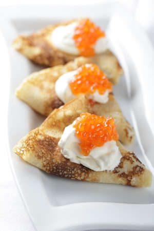 Blinis with sour cream and red caviar photo