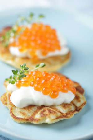 Blinis with red caviar and sour cream photo