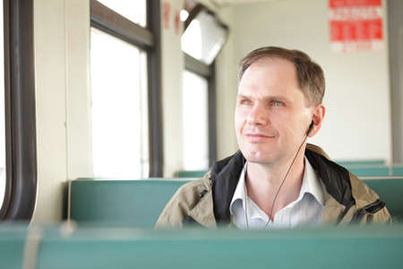 Man listening music with headphones in the train photo
