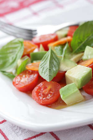 Salad with tomato, avocado, carrot and basil photo