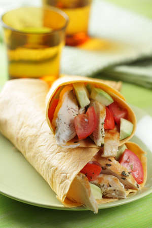 prepared food: Two burritos with chicken, tomato, avocado, and spices