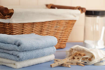 Clothespins in the bag, towels, laundry detergent, and a basket photo