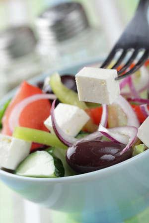 Greek salad with kalamata olives in the bowl closeup photo