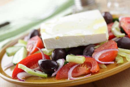 Greek salad with kalamata olives on the plate closeup photo