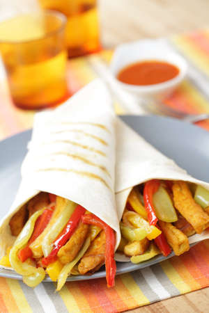 Burritos with tofu, green and red pepper, and carrot photo