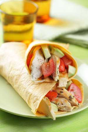 Two burritos with chicken, tomato, avocado, and spices