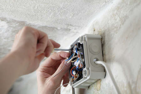electrical contractor: Worker installing the plastic electrical box on the wall