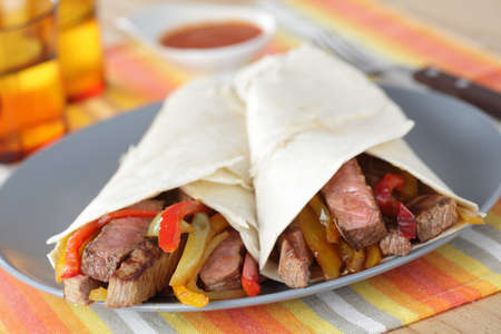 tortilla: Beef steak burritos with vegetables on the plate