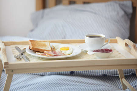 wooden bed: Tray with breakfast on the bed