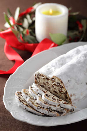 Christmas stollen with raisins against Christmas wreath and candle photo