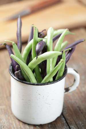 Green and purple string bean in the vintage mug Stock Photo - 10477961