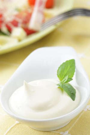 mayonesa: Mayonesa con hoja de albahaca en la taza salsa de