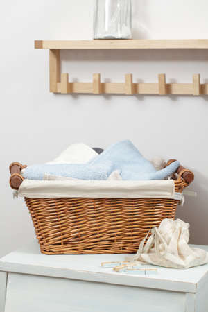 Basket with towels and clothespins in the bag in laundry room photo